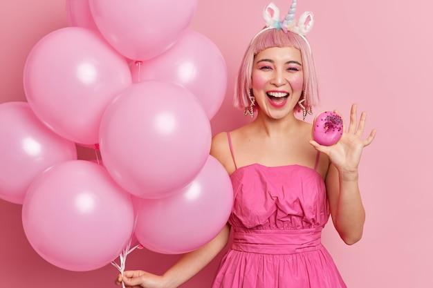 Фотография радостной молодой азиатской женщины с розовыми волосами, одетая в праздничное платье, держит восхитительный глазированный пончик, а куча надутых шаров наслаждается вечеринкой.