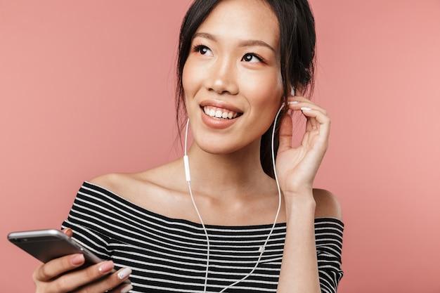 스마트폰을 들고 빨간 벽에 격리된 이어폰으로 음악을 듣는 기본적인 옷을 입은 즐거운 아시아 여성의 사진