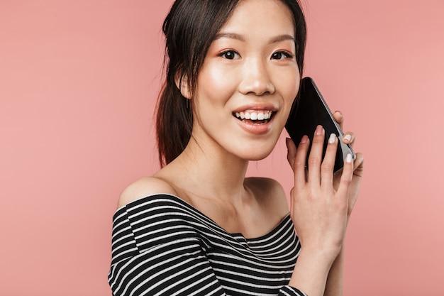 기본 옷을 입고 웃고 있는 즐거운 아시아 여성의 사진과 빨간 벽에 격리된 스마트폰으로 이야기