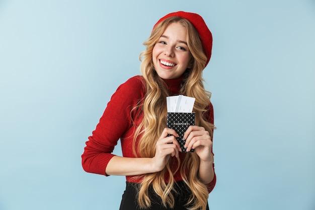 Фото радостной блондинки 20-х годов в красном берете с изолированным паспортом и проездным билетом