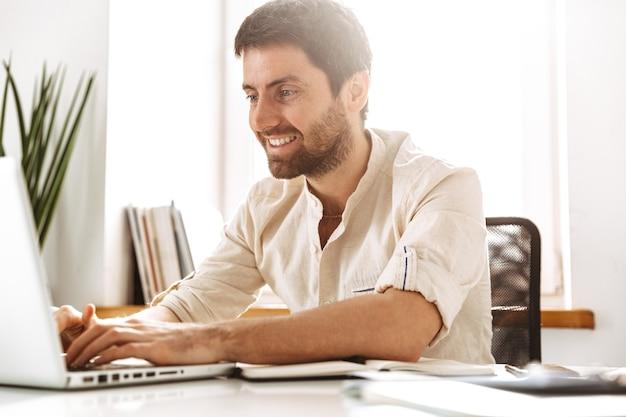 Фотография радостного бизнесмена 30-х годов в белой рубашке, работающего с ноутбуком и бумажными документами, сидя в ярком офисе