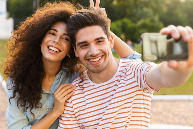 도시 공원에서 스쿠터에 함께 앉아있는 동안 휴대 전화에 셀카를 복용하는 즐거운 커플의 사진