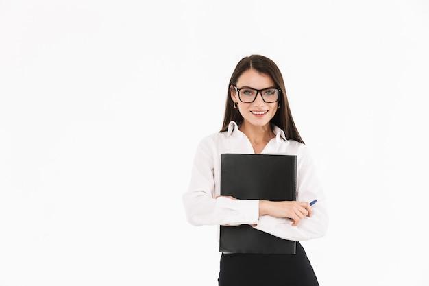 Фотография радостной женщины-деловой женщины, одетой в формальную одежду, держащей переплетчик с документами во время работы в офисе, изолированной над белой стеной