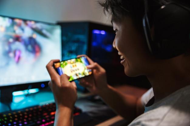 暗い部屋で携帯電話とコンピューターでビデオゲームをプレイし、ヘッドフォンを着用し、バックライト付きのカラフルなキーボードを使用して楽しいゲーマーの少年の写真