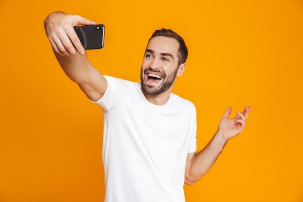 Фотография радостного парня 30-х годов в повседневной одежде, смеющегося и делающего селфи на мобильном телефоне, изолирована