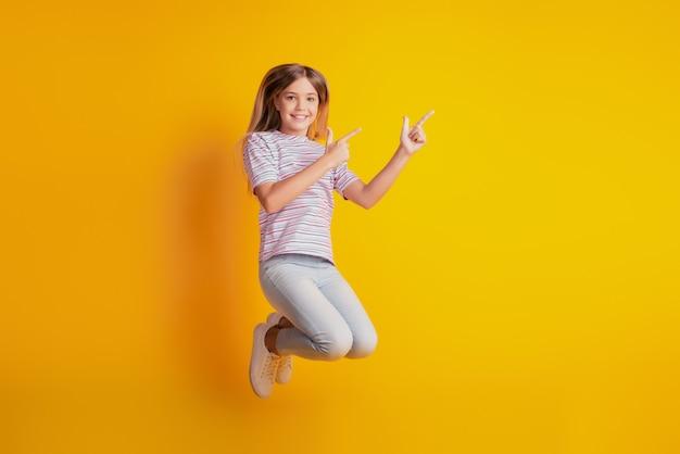 Фотография прыгающей старшеклассницы указывает пальцем на пустое пространство, изолированное на желтом фоне
