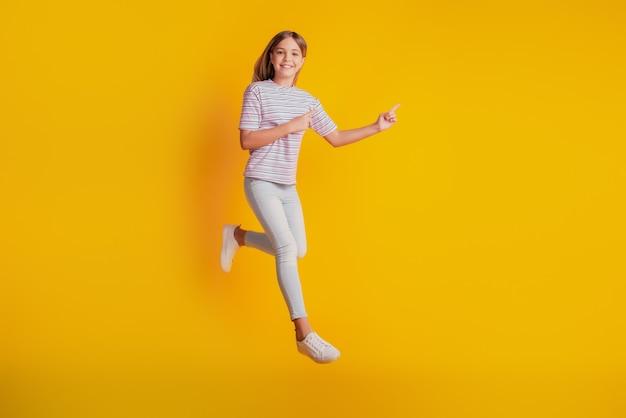 Фотография прыжков бегущей старшеклассницы указывает пальцем на пустое пространство, изолированное на желтом фоне