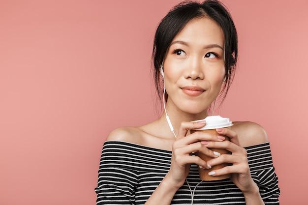 기본 옷을 입은 친절한 아시아 여성이 종이컵을 들고 빨간 벽에 격리된 이어폰으로 음악을 들으면서 옆을 바라보고 있는 사진