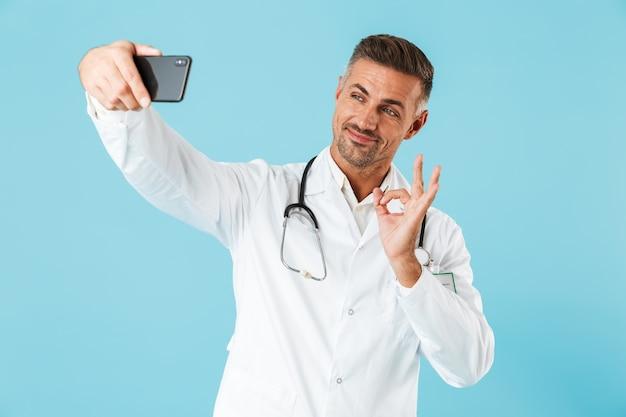 白衣と聴診器を身に着けている親切な医師がスマートフォンで自分撮りをしている写真、青い壁の上に孤立して立っている