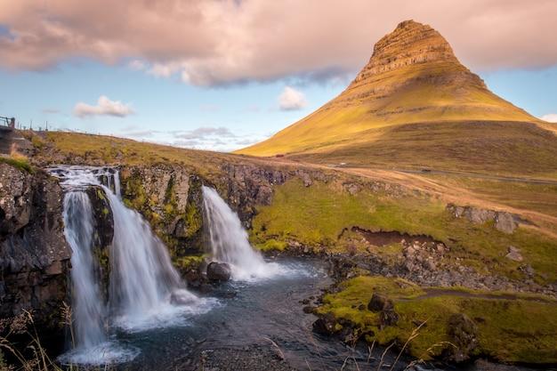 Фотография вулкана киркьюфелл и его водопада утром на востоке исландии.