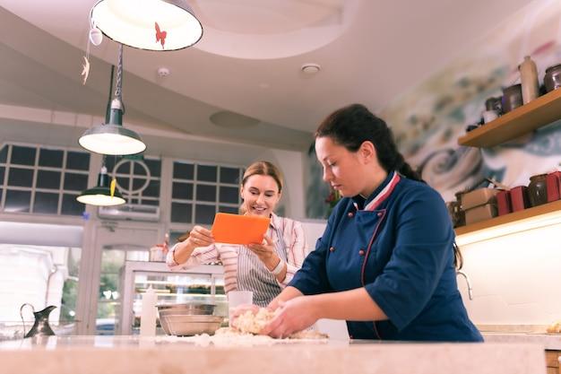 キッチンの写真。オレンジ色のタブレットを使用してキッチンの仕事の写真を作るブロンドの髪の実業家