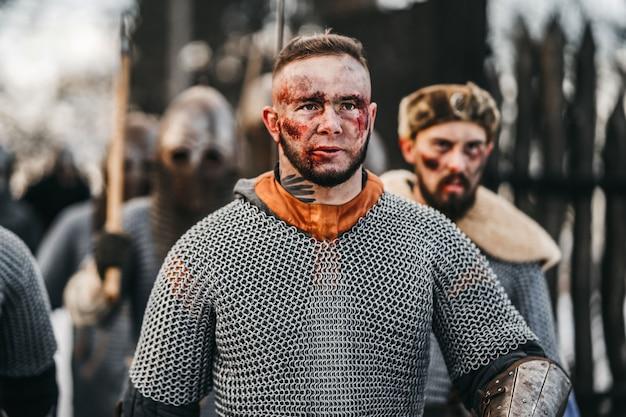 戦争中の剣を持つ鎧の騎士の写真。剣との戦いに行く戦士の邪悪な感情
