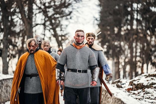 Фотография рыцарей в доспехах с мечами во время войны. злые эмоции воина, который отправляется на битву с мечом