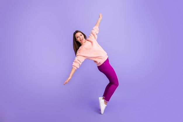 Фотография танцующей леди носить меховой свитер кроссовки изолированы на фиолетовом цветном фоне