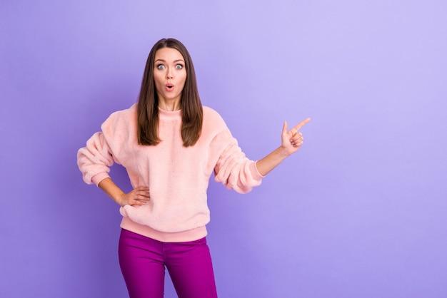 Фотография женщины с открытым ртом, указывающей пальцем на пустое пространство на фиолетовом фоне