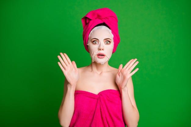 안면 마스크를 사용하는 여자 친구의 사진은 화장하지 않고 그녀를 봅니다. 긴장된 상황 수건 몸 머리는 녹색 배경에 고립