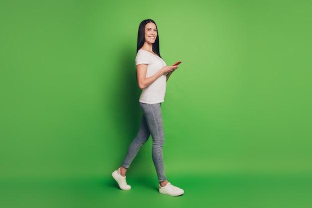 手で電話を持って歩いている女性の写真孤立した緑の背景