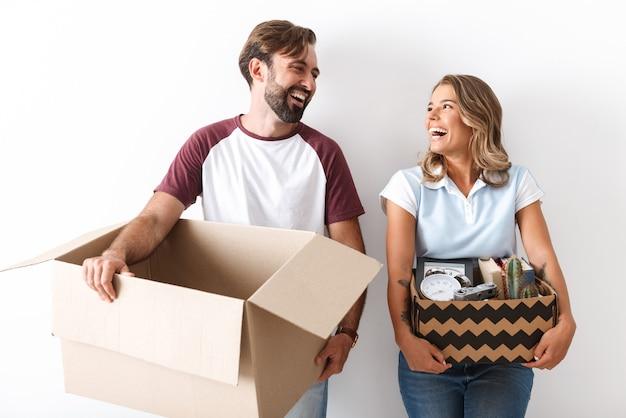 白い壁の上に隔離されたお互いを見ながら段ボール箱を保持しているカジュアルな服を着て笑っているカップルの写真