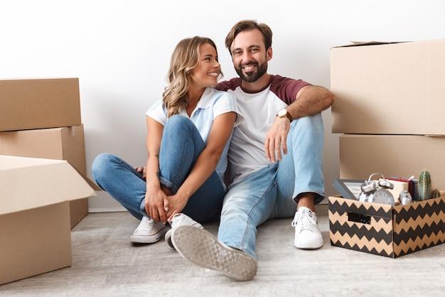 白い壁に隔離された段ボール箱の近くに座って抱き締めてカジュアルな服を着て笑っているカップルの写真