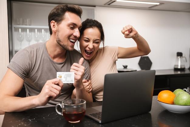 Фотография смеющейся пары мужчины и женщины, использующей ноутбук с кредитной картой, сидя на кухне