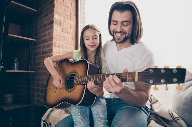 小さな愛らしいかわいい女の子とハンサムな魅力的な若いパパの写真は、窓枠に座ってアコースティックギターを保持します新しいパートソングを学びます屋内で家の部屋に時間を費やします