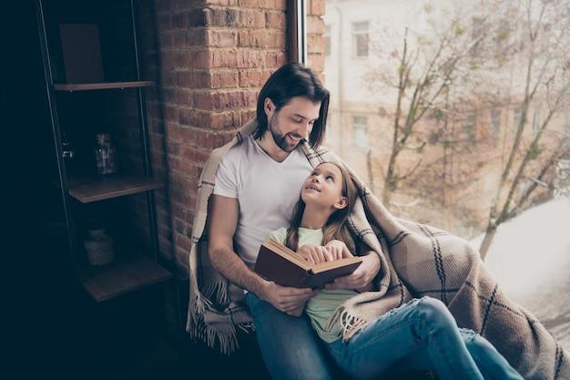小さな愛らしいかわいい女の子とハンサムな若いパパが本を読んでいる写真おとぎ話は窓枠に座って週末を過ごす家庭的な雰囲気は屋内で毛布の家の部屋を覆った
