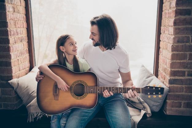 小さな愛らしいかわいい女の子とハンサムな若いパパの写真は、窓枠に座ってアコースティックギターを保持し、新しいコードを教えて週末の家の部屋を屋内で過ごします