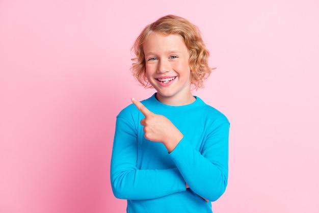 Фотография маленького мальчика указывает пальцем на пустое пространство, носить синюю водолазку, изолированный пастельный розовый цвет фона