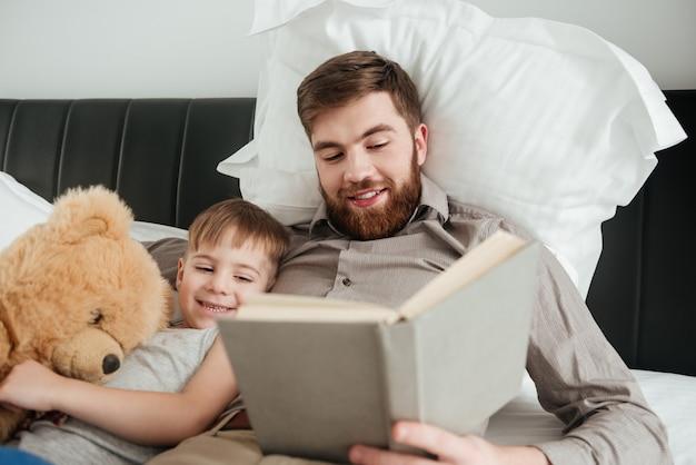 Фотография маленького мальчика лежит дома в постели возле игрушки с его бородатым отцом, читающим сказку.