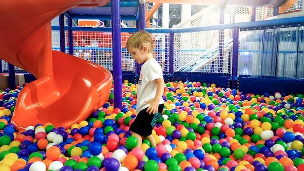 다채로운 플라스틱 공으로 가득 찬 수영장에서 노는 어린 소년의 사진. 쇼핑몰 놀이터에서 즐겁게 노는 유아