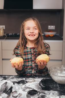 Фото маленькой милой девушки, улыбающейся и держащей тесто на кухне