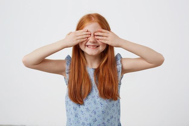 小さなそばかすの写真2つの尾を持つ赤い髪の少女、笑顔と手のひらで目を覆い、青いドレスを着て、ピンクの背景の上に立っています。