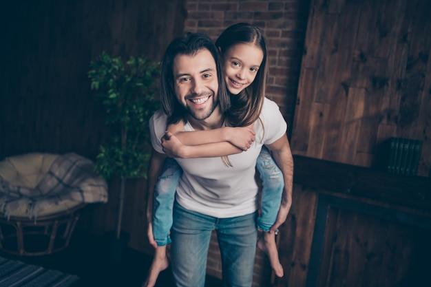 Фото маленькой напуганной красивой девушки возбужденного красивого папы везет дочь на спине, играя в игры хорошее настроение, проводит свободное время