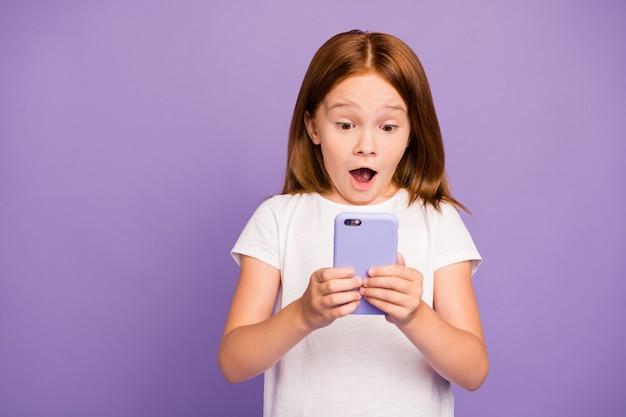 Фотография маленькой рыжей девочки, держащей телефон с открытым ртом