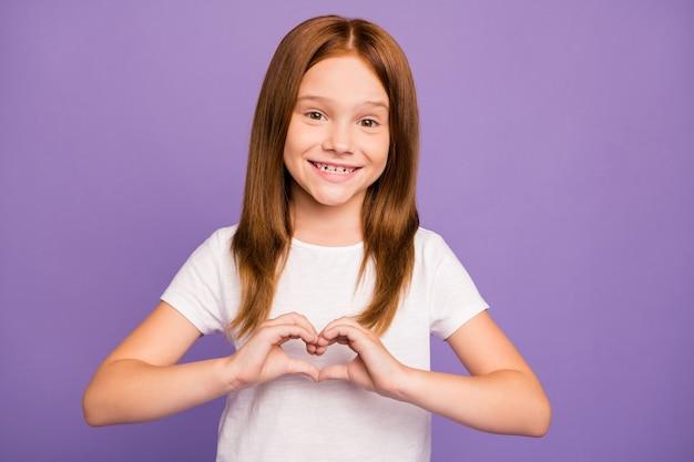 손가락으로 심장 제스처를 만드는 작은 생강 소녀의 사진