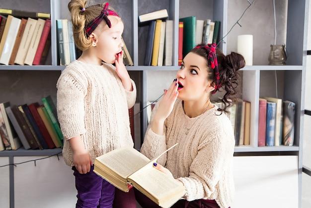 小さな女の子と手に本を驚かせた彼女のお母さんの写真