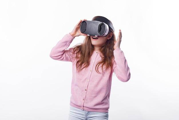 Фотография маленькой девочки, имеющей опыт виртуальной реальности над белой
