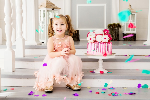 Фотография маленькой девочки в розовом платье сидит на ступеньках рядом с тортом