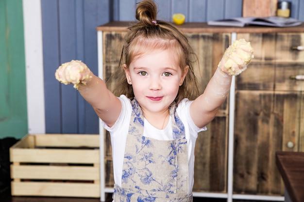 어린 소녀의 사진은 반죽에 더러운 손을 보여줍니다