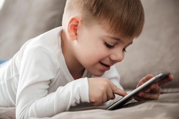 Фотография маленького счастливого мальчика, держащего смартфон и играющего в игру, сидя на диване у себя дома. посмотри на телефон.