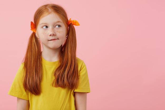 Фотография маленькой думающей рыжеволосой девушки с веснушками с двумя хвостами, смотрит в сторону, трогает щеки, носит желтую футболку, стоит на розовом фоне с копией пространства.