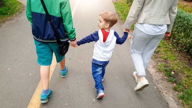 어머니와 형을 손으로 잡고 가을 공원을 걷고 있는 어린 소년의 사진