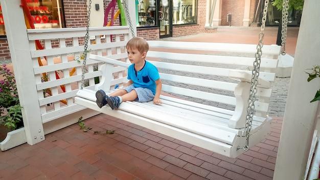 Фотография маленького мальчика-малыша, сидящего на белой деревянной скамейке-качелях на улице старого европейского города