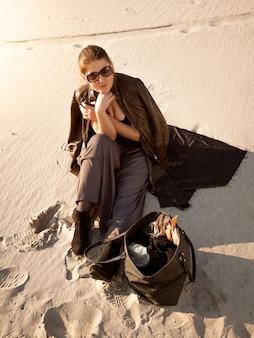 Фотография одинокой женщины, сидящей на песчаной дюне с сумкой