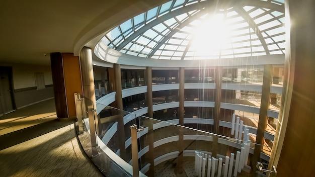 モダンなオフィスビルやホテルの長い廊下と美しいガラス屋根の写真。屋根から差し込む太陽