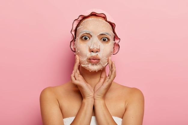 사랑스러운 아시아 여성의 사진은 얼굴에 영양 보습 종이 마스크를 가지고 있고, 뺨을 부드럽게 만지고, 입술을 접고, 분홍색 샤워 캡을 쓰고, 혼자 서 있습니다. 스킨 케어 및 뷰티 트리트먼트 개념
