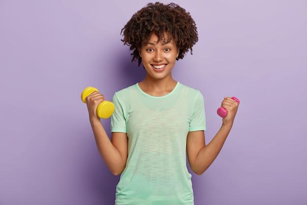 사랑스럽고 쾌활한 강한 여성의 사진은 아령으로 두 팔을 올리고, 팔뚝을 훈련하고, 캐주얼 티셔츠를 입고, 건강하고 적합하고, 이빨 미소로 행복하게 보입니다. 스포츠, 여성의 힘