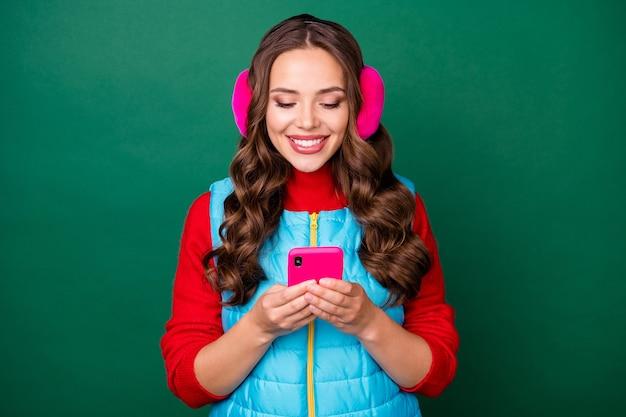 素敵なかわいい若い女性の写真は、電話チャットの友人を保持します良いニュースを共有します光沢のある笑顔待っている応答着用ピンクのイヤーウォーマー青いベスト赤いセーター分離された緑色の背景
