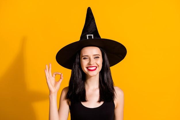 사랑스럽고 귀여운 젊은 마술사 이빨 미소 짓는 미소의 사진은 고객이 응답하는 복장 품질이 검은색 마법사 모자 드레스를 입고 밝은 노란색 배경에 격리되어 있음을 보여주는 손을 들어 올립니다.