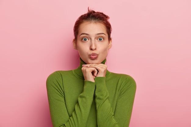 素敵なヨーロッパの女性の写真は、唇を吐き出し、緑のタートルネックを身に着け、化粧をせず、両手をあごの下に置き、カメラに顔をしかめる、ピンクのスタジオの壁に隔離されています。
